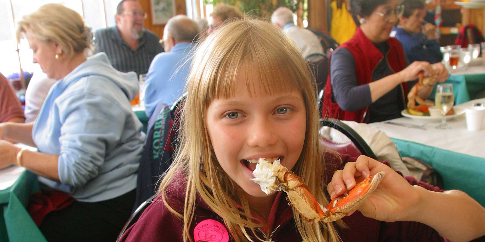 a girl eating crab inside a restaurant