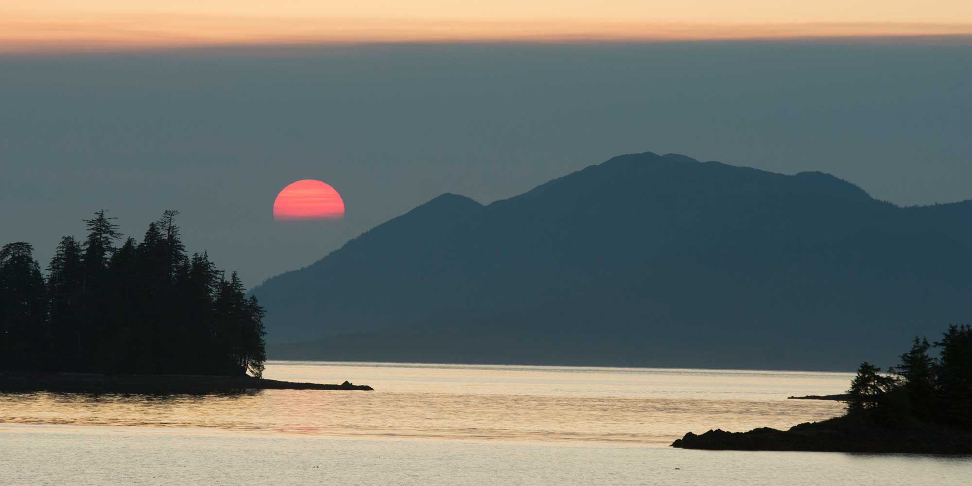 sunset over water with mountains and trees in silhouette