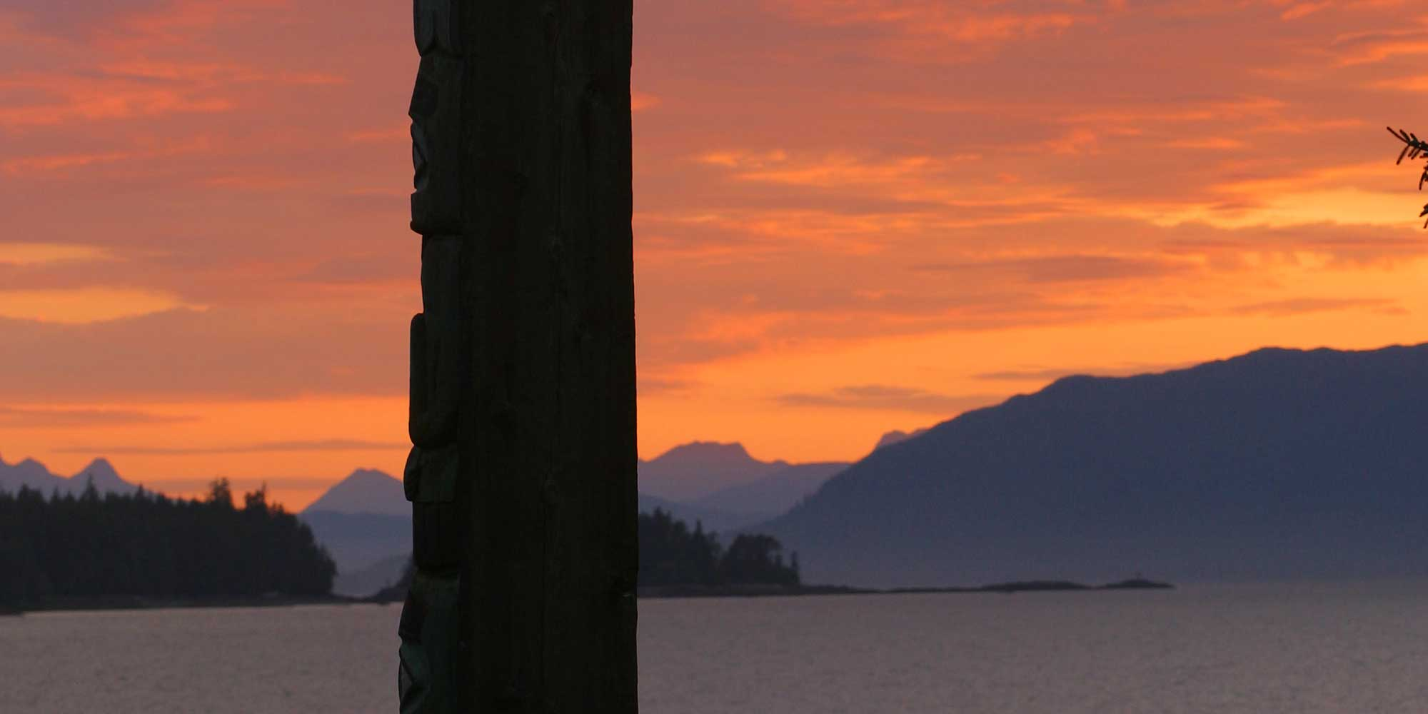 sunset with the silhouette of a totem pole in the foreground and mountains in the background